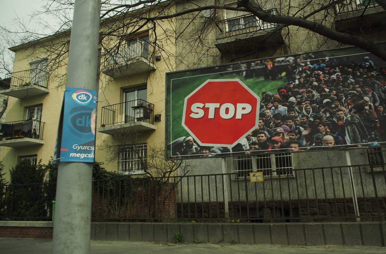 """Kevään vaaleissa Unkarin hallitus kampanjoi julisteilla, joissa näkyy turvapaikanhakijoita ja sana """"STOP"""". Kuvassa myös opposition revitty vaalijuliste. Kuva: Emilia Palonen"""