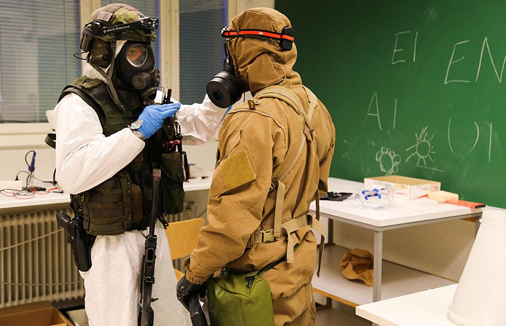 Kokemuksia ja parhaita käytänteitä hybridiuhkiin vastaamiseksi voidaan välittää myös siviilien ja sotilaiden yhteisharjoituksissa sekä kansainvälisissä harjoituksissa. Kuvassa suomalaiseen suojelun erikoisosastoon (SEO) kuuluva sotilas selostaa tilannetta norjalaiselle kollegalleen Porin prikaatin johtamassa pohjoismaisessa suojeluharjoituksessa Reccex 17. Kuva: Puolustusvoimat