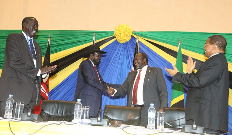Former Vice President Dr. Riek Machar and President Salva Kiir of South Sudan shake hands after signing the Arusha Reconciliation Agreement, as President Jakaya Kikwete of Tanzania (left) and Mr. Deng Alor Kuol, former Foreign Minister of South Sudan, look on. Photo by Tanzania State House, Arusha, 21 January 2015.