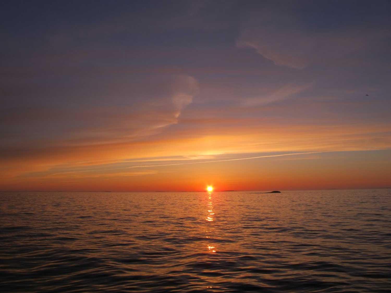 Auringonlaskumaisema merellä Vrow Maria -kauppa-aluksen hylyn yläpuolella.