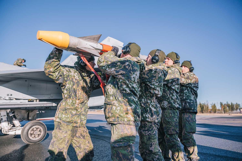 Viisi reserviläistä nostaa ohjusta Hornet-hävittäjään.