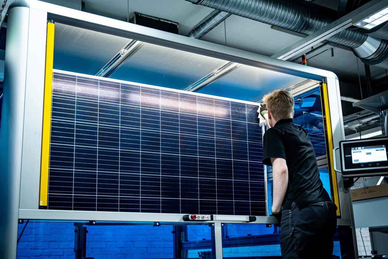 Työntekijä tarkastaa ja puhdistaa valmistunutta aurinkopaneelia tehtaalla.