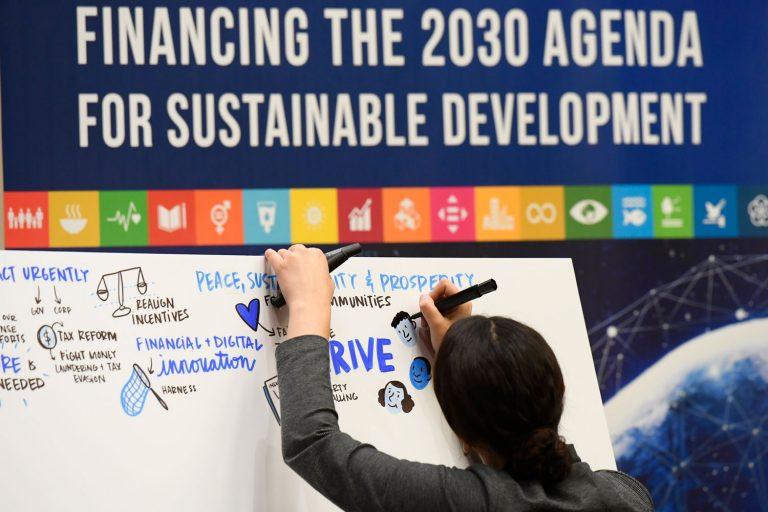 Ihminen piirtää taululle ajatuksia agenda 2030:n kestävän kehityksen tavoitteiden toteuttamisen rahoitukseen liittyen.