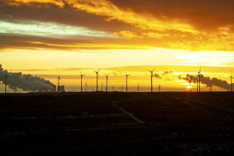 Kuvan etualalla ruskohiiliavolouhos, taustalla tuulivoimaloita ja savuttava hiilivoimala auringonlaskussa.