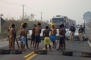 Kayaopa-alkuperäiskansan edustajia renkaista ja laudoista rakentamansa tiesulun keskellä. Myös poliisi on paikalla. Tiesulun takana banderollin jälkeen on jonossa kuorma-autoja.
