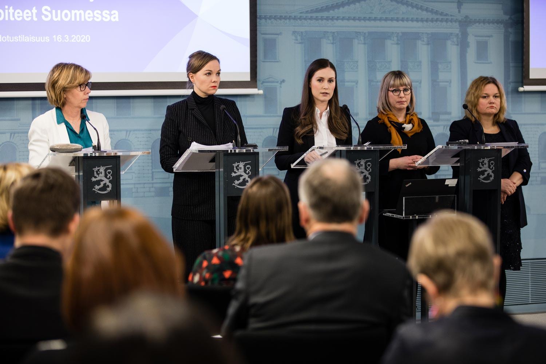 Ministerit Henriksson, Kulmuni, Marin, Pekonen ja Kiuru hallituksen tiedotustilaisuuden aikana. Etualalla näkyy istuvia muita ministereitä, virkamiehiä ja median edustajia.