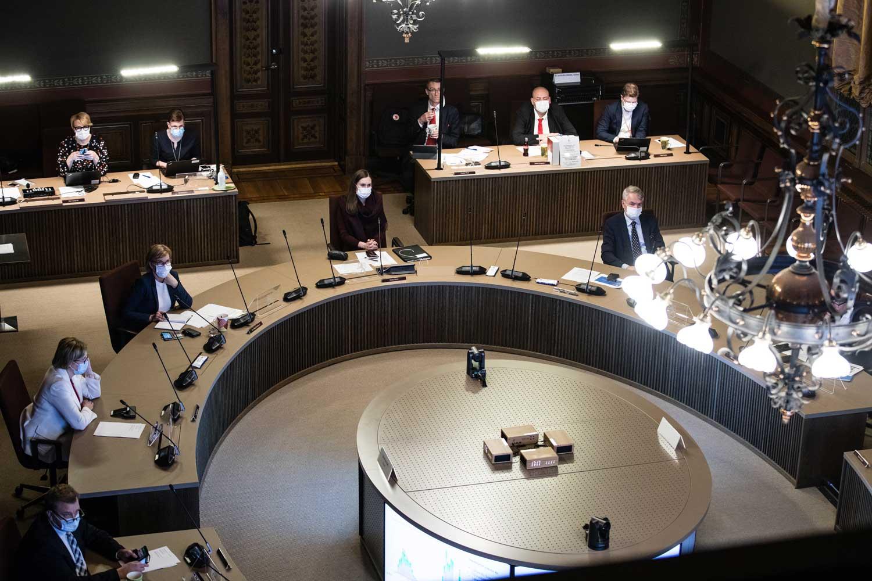 Hallitus kokoontunut säätytalolle pyöreän pöydän äärelle. Taustalla keskeisen virkamieskunnan edustajat. Kaikilla on päässään maskit.