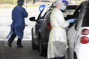 Suojavarusteisiin pukeutuneet hoitajat ottavat koronavirusnäytteitä autolla testaukseen saapuneilta.