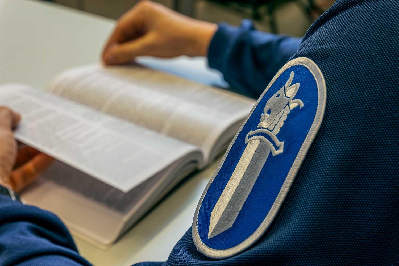 Kuvassa näkyy poliisiopiskelijan virkatunnus hihassa ja kirja, jota opiskelija lukee.
