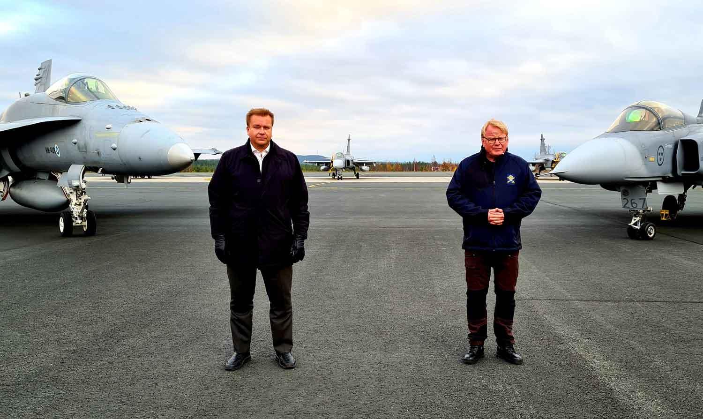 Suomalainen ja ruotsalainen hävittäjälentokone reunustavat keskellä seisovia Suomen ja Ruotsin puolustusministereitä Antti Kaikkosta ja Peter Hultqvistiä.