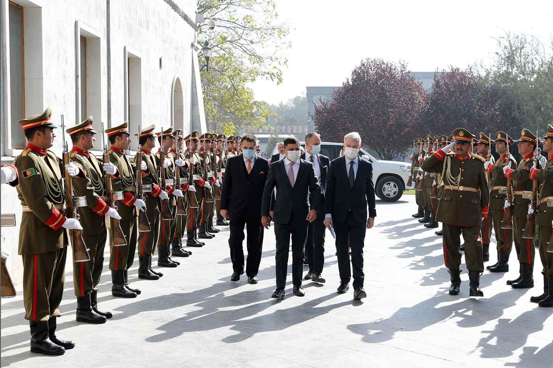 Ulkoministeri Pekka Haavisto kävelee presidentin neuvonantajan ja saattueen kanssa sotilaiden kunniakujan keskellä Afganistanin presidentin vastaanotolle.