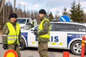 Edessä kaksi virka-aputehtävässä olevaa varusmiestä, joilla maastopukujen päällä on huomioliivit ja toisella kädessä pysäytyskyltti. Taustalla poliisin virka-autoja.