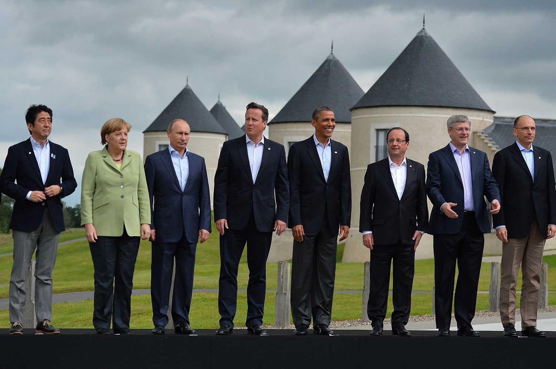 Kuvassa G8-maiden johtajat ryhmäkuvaa järjestäytymässä. Taustalla näkyy nurmea, linna ja harmaa taivas.