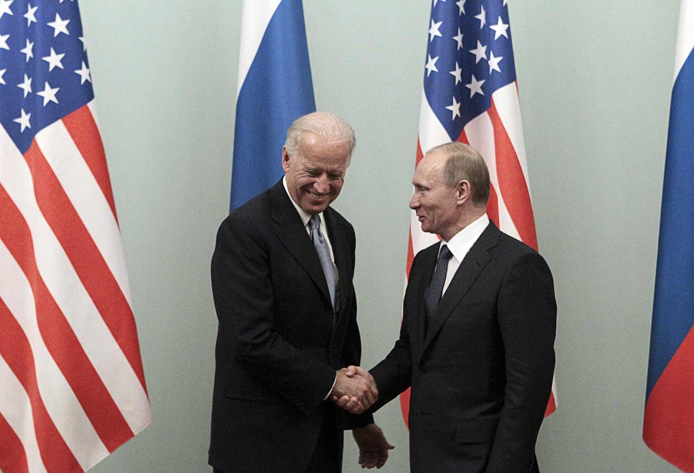 Biden ja Putin kättelevät. Taustalla Yhdysvaltojen ja Venäjän liput.