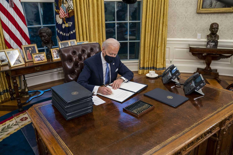 Joe Biden istuu työpöytänsä takana Oval Officessa ja allekirjoittaa päätöksiä.