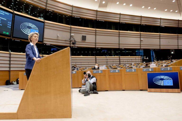 Euroopan komission puheenjohtaja puhuu puhujapöntössä kameramiehen ottaessa kuvaa.