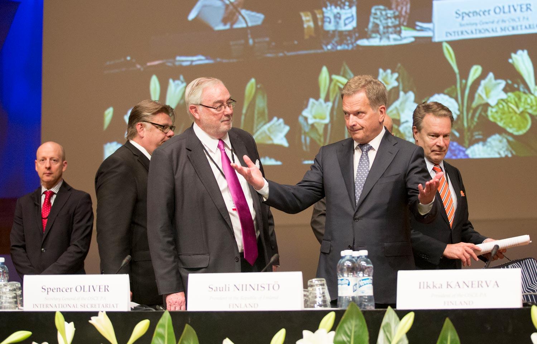 Presidentti Niinistö nostaa käsiään Finlandia-talon lavalla Etyjin yleiskokouksessa.