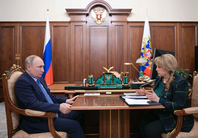 Presidentti Putin vasemmalla ja keskusvaalilautakunnan puheenjohtaja Pamfilova oikealla istumassa pöydän ääressä Pamfilovan puhuessa. Taustalla Venäjän liput.