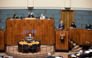 Ulkoministeri Pekka Haavisto eduskunnan istuntosalin puhujapöntössä puhemiehistön ja muiden ministerien istuessa hänen takanaan.