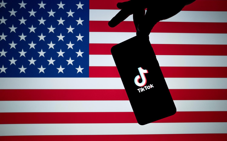 Käsi pitelee Yhdysvaltojen lipun edessä puhelinta, jonka ruudulla on Tiktok-palvelun logo.