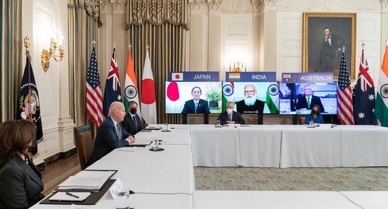 Joe Biden istuu pöydän takana esikuntansa istuessa etäänpänä. Ruuduilla kokoukseen osallistuvat Japanin, Intian ja Australian johtajat maidensa lippujen ympäröiminä.