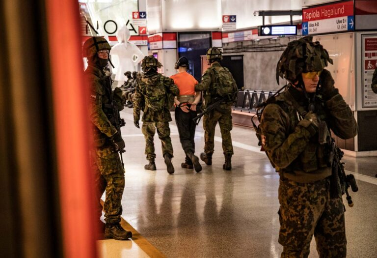 Maastopukuiset sotilaat harjoittelevat metroasemalla. Kiinniotettavaa esittävää siviiliä talutetaan pois kädet sidottuina.