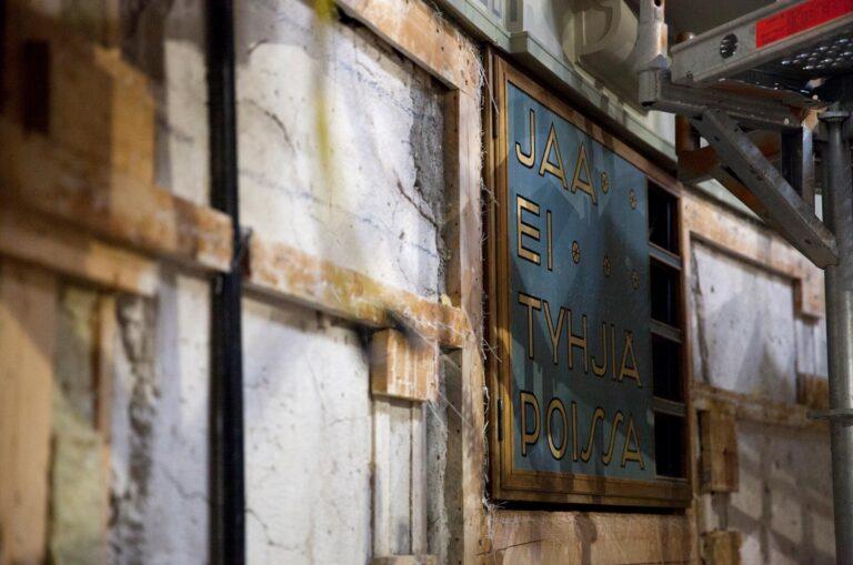 Eduskunnan äänestystuloksen näyttävän taulun ympäriltä on irroitettu seinän pintamateriaali paljaalle betonille ja laudoille Eduskuntatalon remontin aikana.