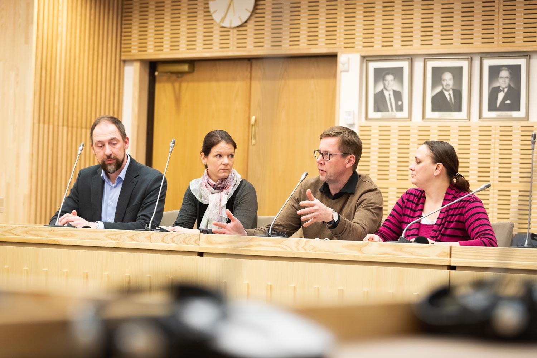 Neljä kansalaisraadin jäsentä istuvat valtuustosalissa keskustelemassa.