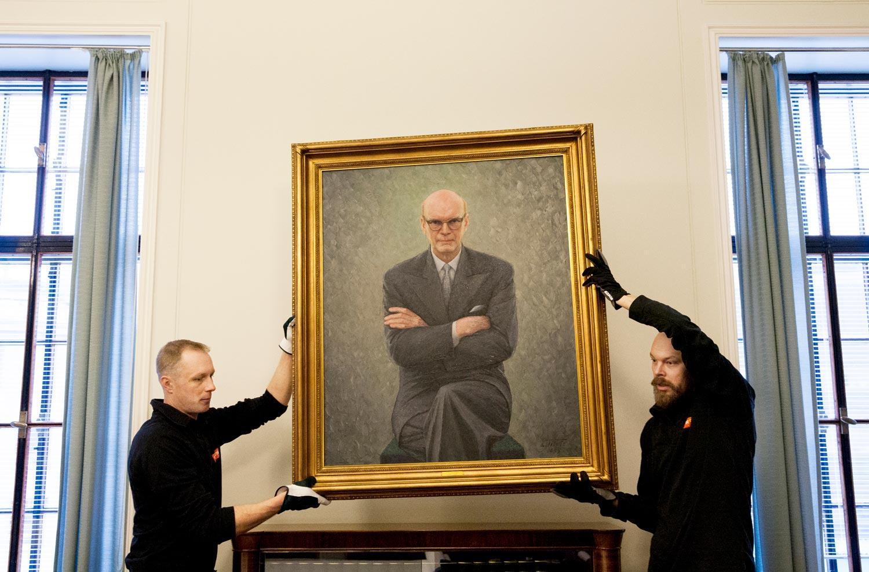 Kaksi miestä nostaa puhemies Kekkosta esittävän muotokuvan seinältä.