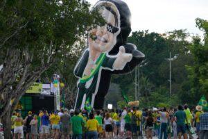 Brasilian lipun väreihin pukeutuneet mielenosoittajat ympäröivät monikymmenmetristä presidentti Bolsonaroa esittävää kylttiä.