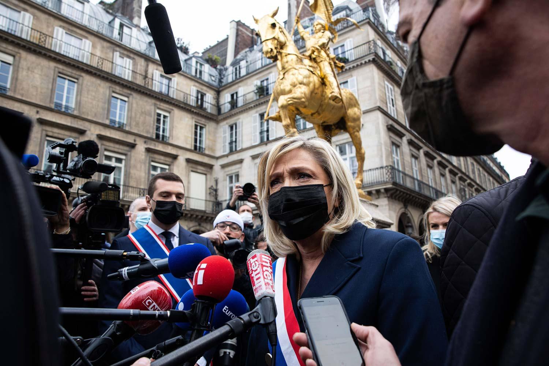 Marine Le Pen puhuu median mikrofonien edessä taustallaan Jeanne d'Arcin patsas Pariin keskustassa.