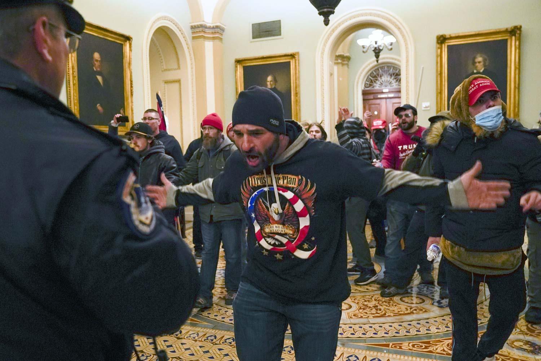 Yhdysvaltain kongressiin sisälle päässeitä mellakoitsijoita, joista keskimmäisellä on QAnon-aiheinen paita.